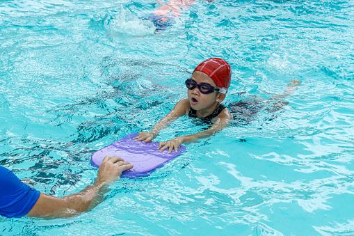 kids learn how to swim in swimming class